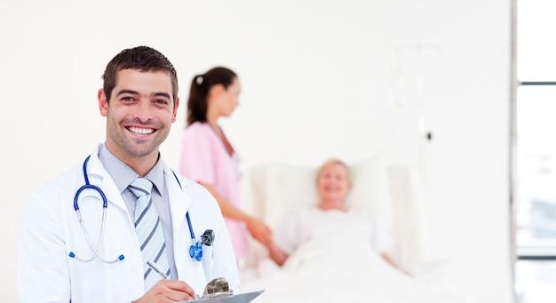 Medico felice che tiene una scheda di clip