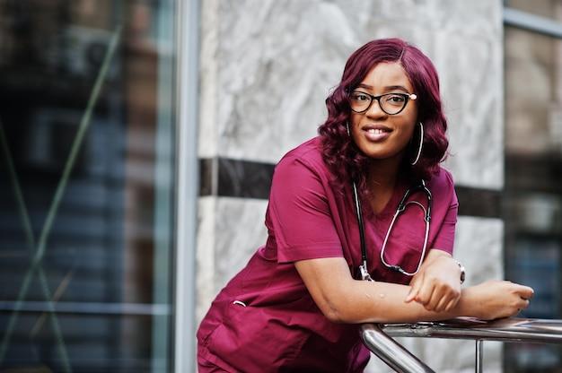 Medico femminile afroamericano all'uniforme rossa del laboratorio con lo stetoscopio. concetto di medicina, professione e assistenza sanitaria.