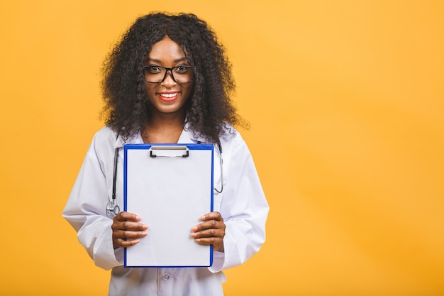 Medico femminile afroamericano sorridente in camice bianco con appunti e stetoscopio