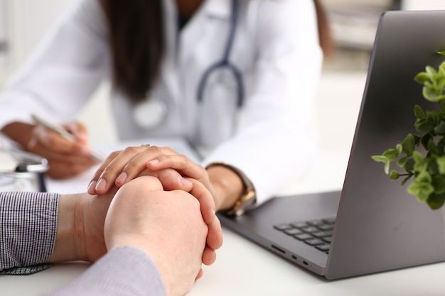 Medico femminile amichevole che tiene la mano paziente maschio