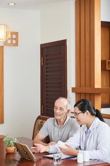 Medico femminile asiatico che consulta paziente maschio caucasico senior a casa