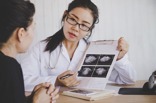 Medico femminile asiatico che spiega immagine medica dei raggi x al paziente