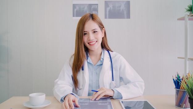 Medico femminile asiatico sicuro che si siede alla scrivania e che sorride alla macchina fotografica