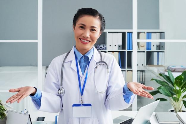 Medico femminile asiatico sorridente che posa nell'ufficio