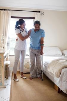 Medico femminile che aiuta uomo senior a camminare con il camminatore in camera da letto