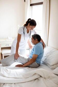 Medico femminile che assiste paziente senior in camera da letto
