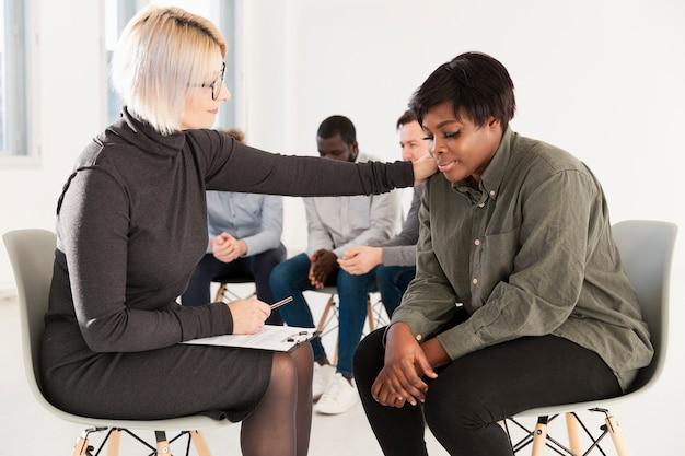Medico femminile che consola il paziente afroamericano