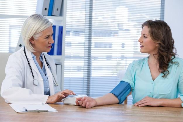 Medico femminile che controlla pressione sanguigna di un paziente