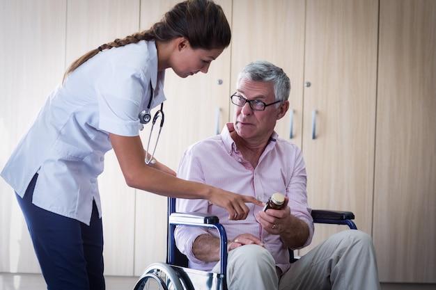 Medico femminile che dà medicina all'uomo senior