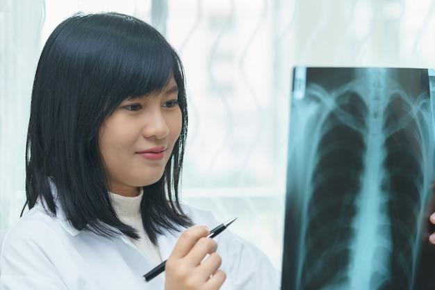 Medico femminile che esamina i polmoni con il film dei raggi x