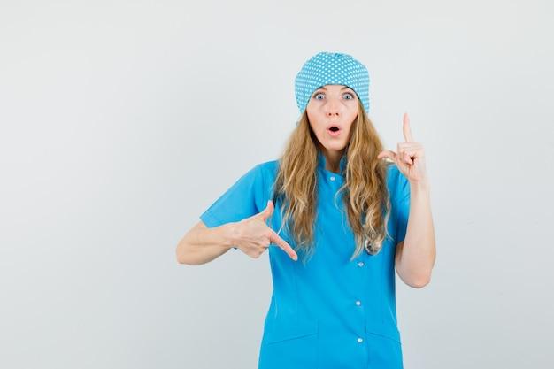 Medico femminile che indica le dita su e giù in uniforme blu e guardando meravigliato.