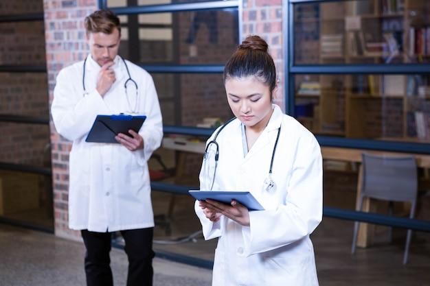 Medico femminile che per mezzo della compressa digitale vicino alla biblioteca e al dottore maschio che stanno dietro e che pensano