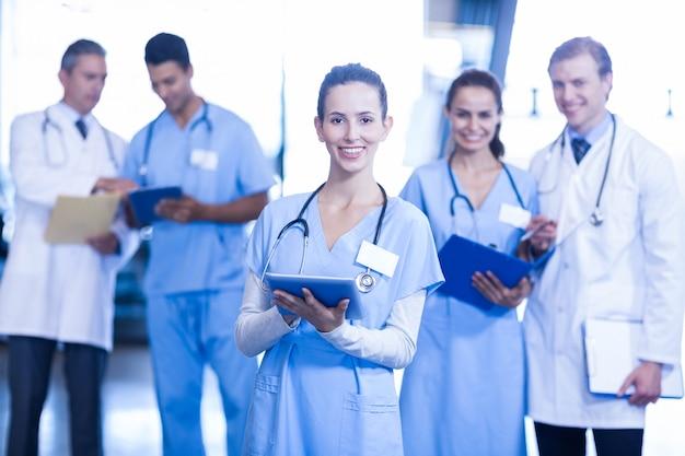 Medico femminile che per mezzo della compressa e sorridendo mentre i suoi colleghi che stanno