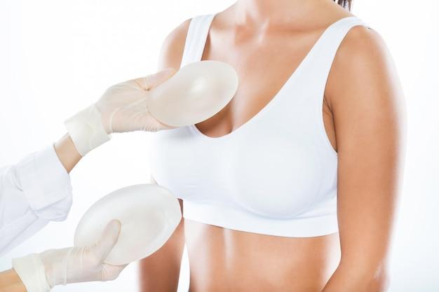 Medico femminile che sceglie la protesi mammaria con il suo paziente sopra fondo bianco.