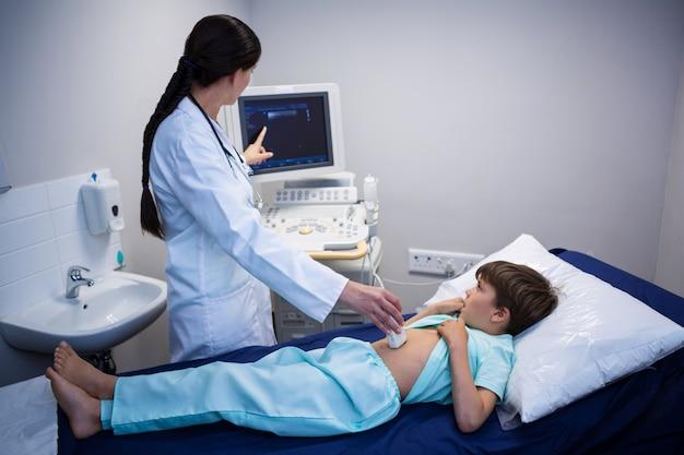 Medico femminile che spiega il rapporto di ecografia al paziente sullo schermo