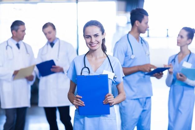 Medico femminile che tiene perizia medica e che sorride mentre discussione dei suoi colleghi