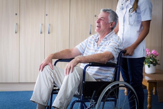 Medico femminile che trasporta uomo maggiore sulla sedia a rotelle