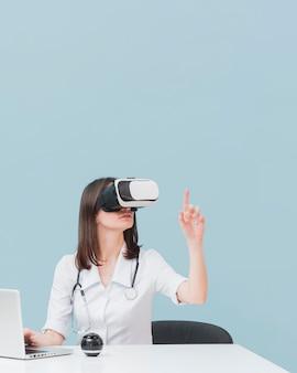 Medico femminile che usando la cuffia avricolare di realtà virtuale con lo spazio della copia