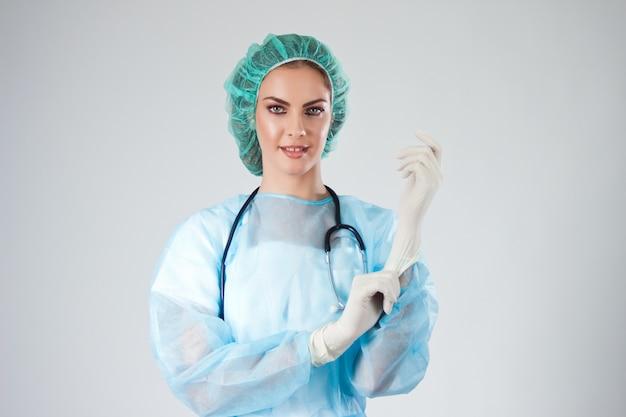 Medico femminile chirurgo in scrub con cappello medico che mette guanti chirurgici.