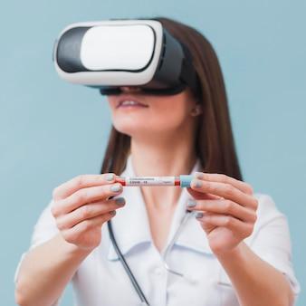 Medico femminile con la cuffia avricolare di realtà virtuale che tiene la provetta del coronavirus