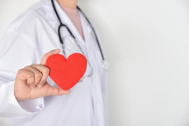 Medico femminile con lo stetoscopio che tiene cuore rosso in sua mano su fondo bianco. condizioni mediche e sanitarie.