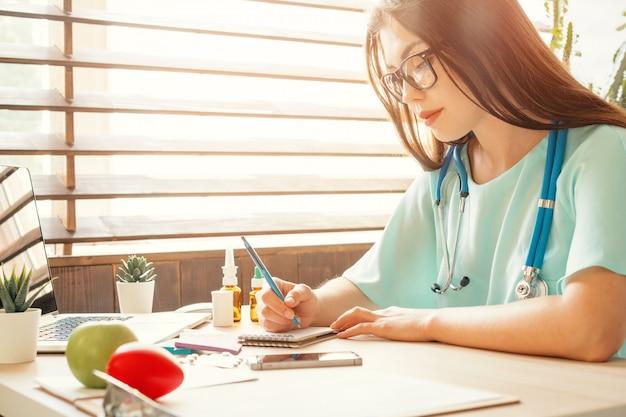 Medico femminile della medicina che riempie forma o prescrizione medica paziente
