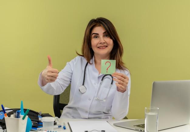 Medico femminile di mezza età soddisfatto che indossa una veste medica con lo stetoscopio che si siede alla scrivania lavora sul computer portatile con strumenti medici che tengono il punto interrogativo della carta il suo pollice in su sulla parete verde