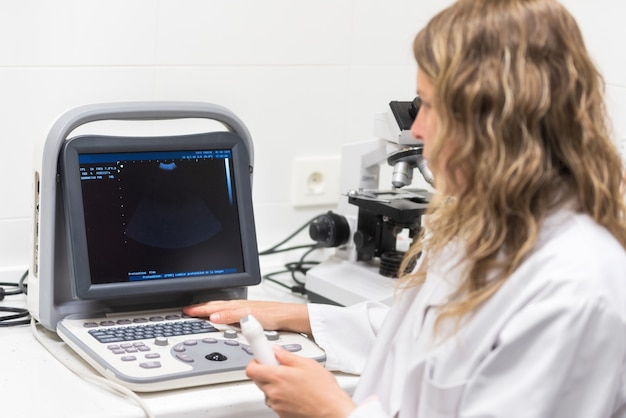 Medico femminile grazioso, posando mentre sta facendo un'ecografia.