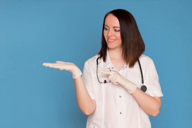 Medico femminile in guanti medici con uno stetoscopio che indica lo spazio della copia su fondo blu