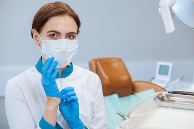 Medico femminile in uniforme che indossa guanti e maschera medici