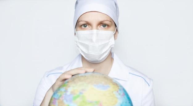 Medico femminile nella mascherina medica protettiva con un globo su una priorità bassa bianca. concetto di pandemia e virus globale.