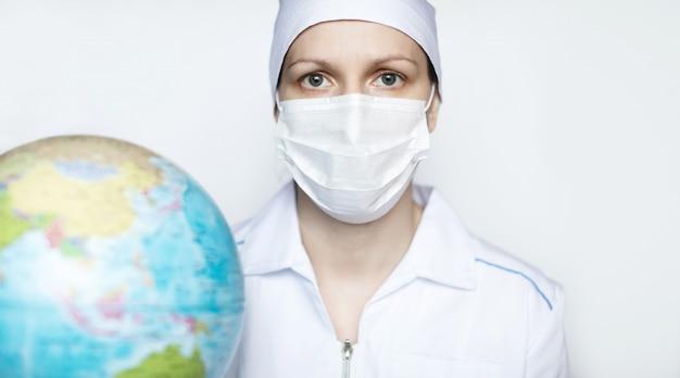 Medico femminile nella mascherina medica protettiva con un globo su una priorità bassa bianca.