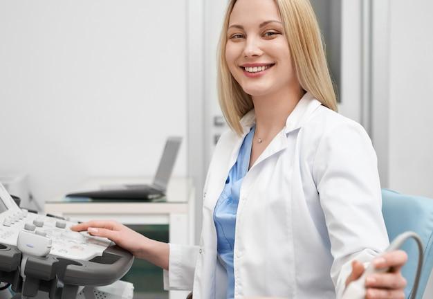 Medico femminile positivo in uniforme bianca che esamina macchina fotografica