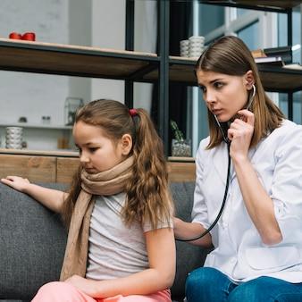 Medico femminile serio che esamina la ragazza ammalata con lo stetoscopio