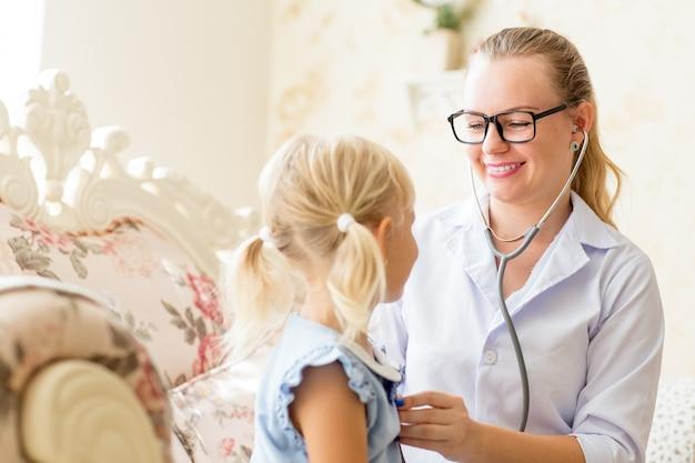 Medico femminile sorridente che ascolta la bambina