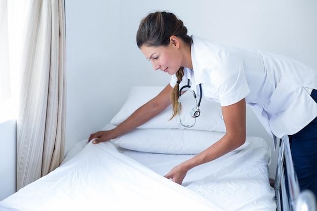 Medico femminile sorridente che prepara il letto