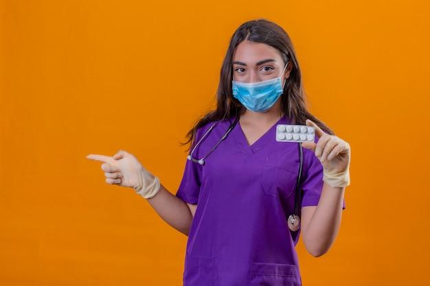 Medico giovane donna in uniforme medica con fonendoscopio indossando maschera protettiva e guanti tenendo blister con pillole e indicando con il dito verso il lato su sfondo arancione isolato
