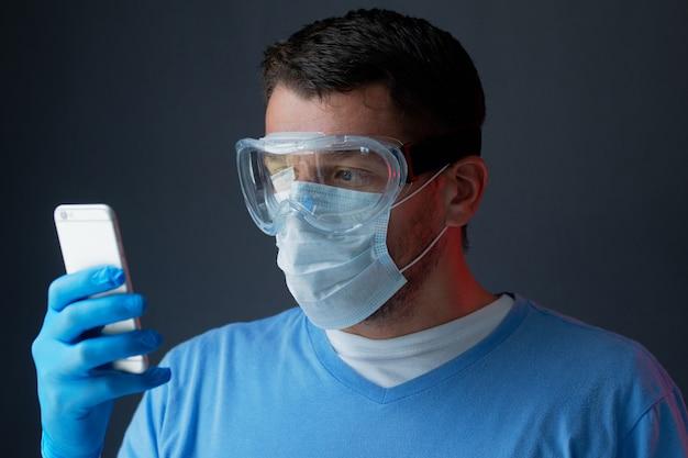 Medico in abito medico guanti maschera e occhiali su sfondo grigio, parlando al telefono. coronavirus epidemico pandemico 2019-ncov, virus covid-19.