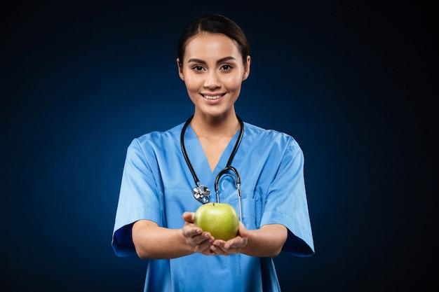 Medico in buona salute felice che giudica mela verde isolata