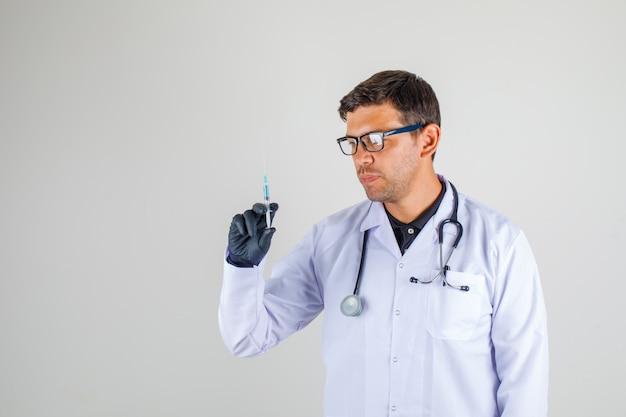 Medico in camice bianco con stetoscopio tenendo la siringa in su