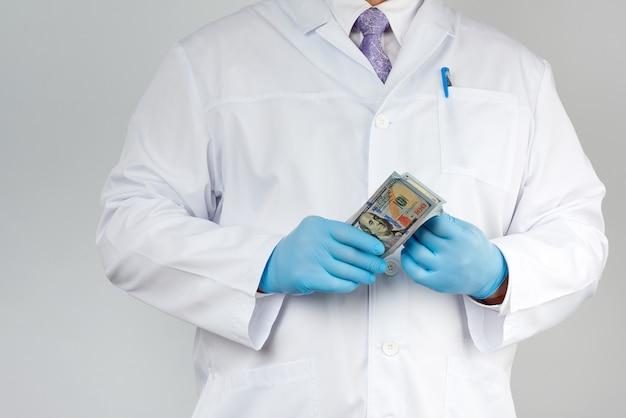 Medico in camice bianco, indossando guanti sterili blu, il medico tiene un pacco di carta moneta, concetto anticorruzione