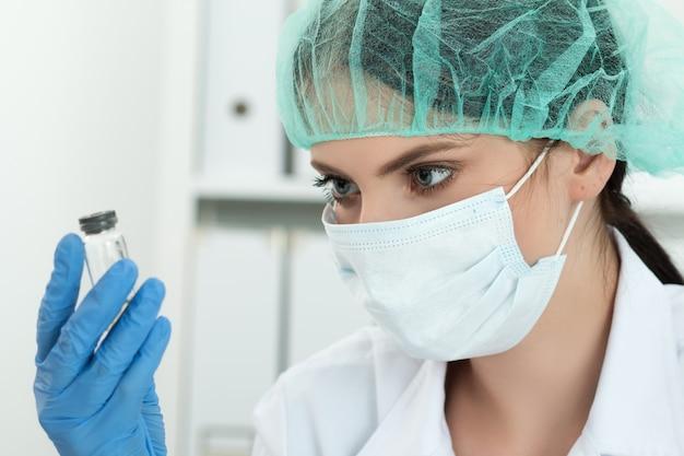 Medico in guanti protettivi e mascherina chirurgica e cappello guardando il piccolo pallone con liquido in laboratorio. ricerca scientifica, assistenza sanitaria e concetto medico.