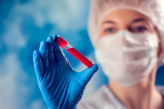 Medico in maschera medica e guanti blu tenendo tubo con analisi del sangue. concetto di medicina e assistenza sanitaria.