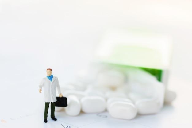 Medico in miniatura in piedi con la medicina.