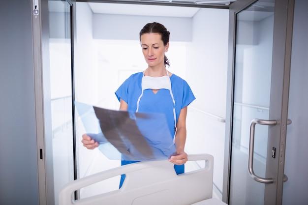 Medico in piedi con il rapporto dei raggi x
