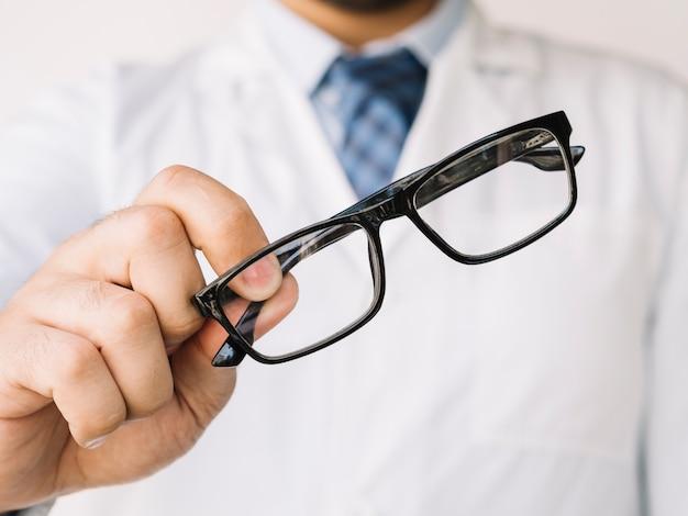 Medico in possesso di un paio di occhiali a forma nera