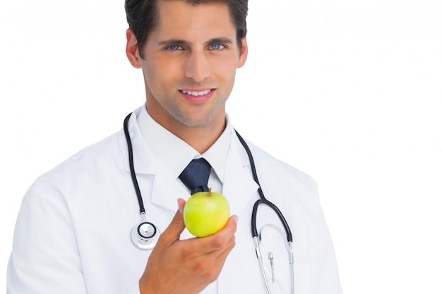 Medico in possesso di una mela e sorridente
