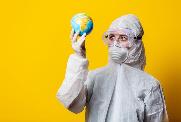Medico in tuta protettiva e maschera tenere globo terrestre