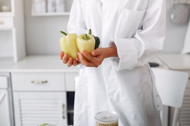 Medico in una cucina con verdure
