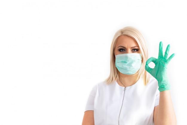 Medico in una maschera medica e guanti di gomma verde. virus, coronavirus. protezione. attrezzature sterili per l'industria medica e della bellezza. copia spazio
